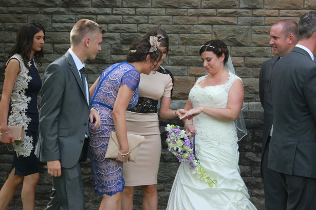 Bride showing her female wedding guest her wedding ring| Purple themed wedding| Rhiannon & Michael's Real Wedding | Confetti.co.uk