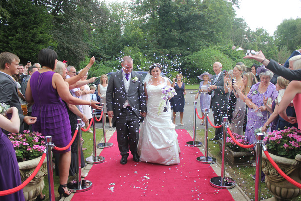 Guests throwing confetti over the newlyweds| Purple themed wedding| Rhiannon & Michael's Real Wedding | Confetti.co.uk