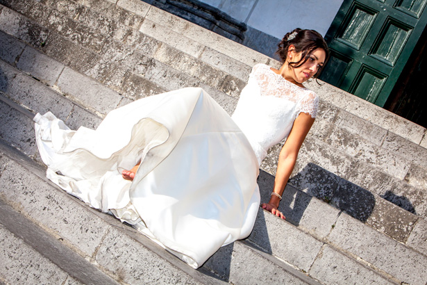 Official wedding shoot by Debbie Sanderson Wedding Photography| Bride in her lace Augusta Jones dress sitting on the footsteps outside Ravello, Italy | Wedding moments you have to capture | Leanne and Chris's Real Italian Wedding | Confetti.co.uk