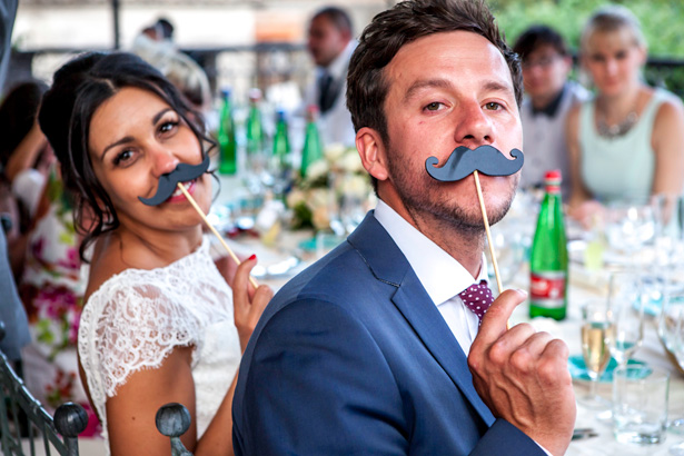 Wedding reception at Villa Maria, Italy | bride and groom holding  comedy moustache| Funny wedding moments to capture | Leanne and Chris's Real Italian Wedding | Confetti.co.uk