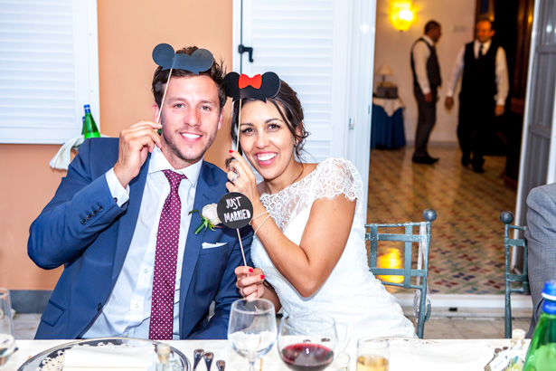 Wedding reception at Villa Maria, Italy | Bride and groom holding comedy Mickey and Minnie mouse props | Leanne and Chris's Real Italian Wedding | Confetti.co.uk