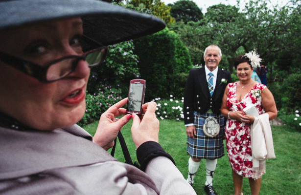 Wedding guests taking pictures of each other on their mobile phone before the ceremony  | Steph and Gary's Real Garden Wedding | Confetti.co.uk