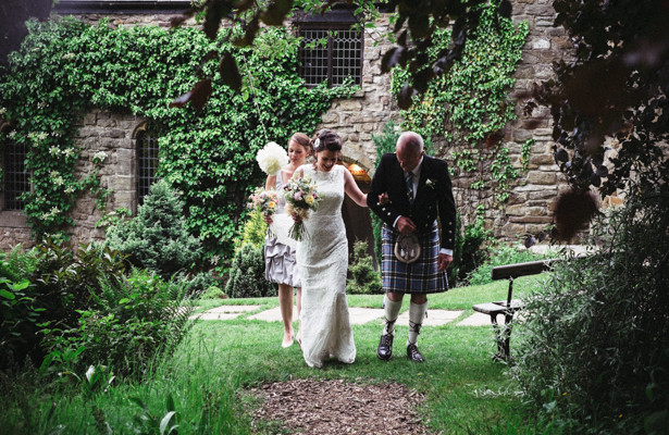 Bride making her way down to the garden ceremony with her father and bridesmaid | Steph and Gary's Real Garden Wedding | Confetti.co.uk