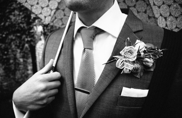 Vintage rose boutonniere  | Wedding guest holding an umbrella | Steph and Gary's Real Garden Wedding | Confetti.co.uk