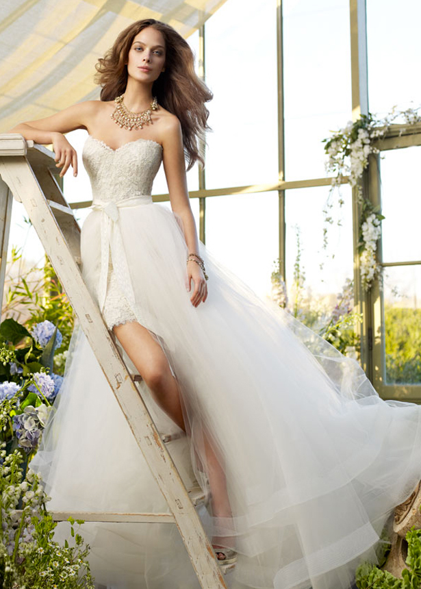 Stunning girl posing next to some vintage ladders in her Tara Keely wedding dress with a floral backdrop
