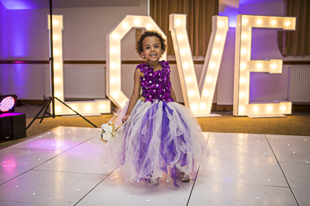 Love marquee lights on the dance floor | Flower girl in her purple dress on the dance floor | Precious and Jerald's real wedding | Confetti.co.uk