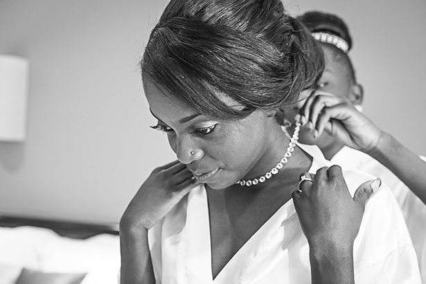 Bridesmaid helping the bride with her necklace | Precious and Jerald's real wedding | Confetti.co.uk
