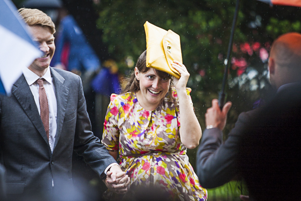 Wedding guests trying to shelter from the rain| Precious and Jerald's real wedding | Confetti.co.uk