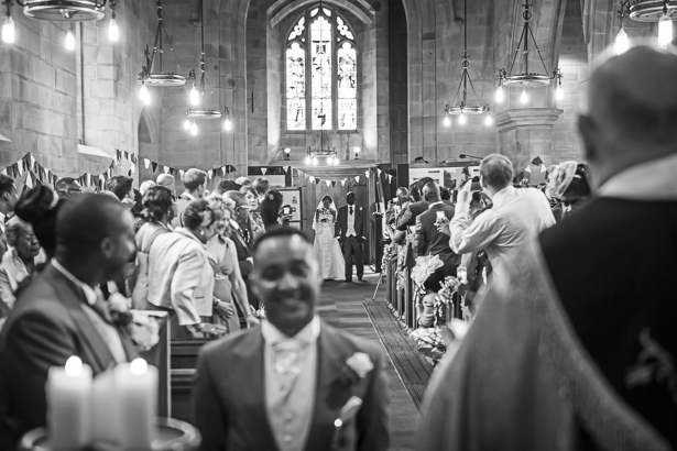 The bride walking down the aisle with her father | Wedding guests taking pictures of the bride as she arrives | The groom waiting for the bride at the altar | Precious and Jerald's real wedding | Confetti.co.uk