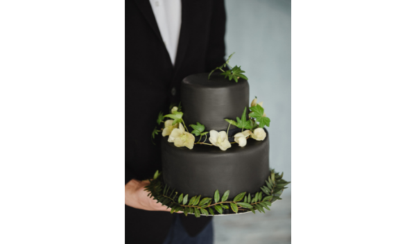 black wedding cake with white flowers and foliage