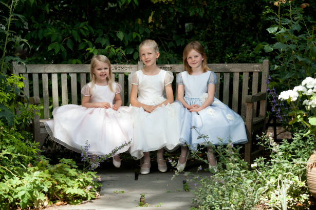 3 Junior bridesmaids sat on a bench | Confetti.co.uk