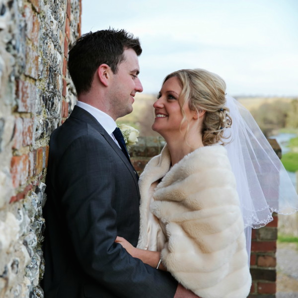 Bride and Groom Stare Lovingly Against an Exposed Brick Wall | Confetti.co.uk