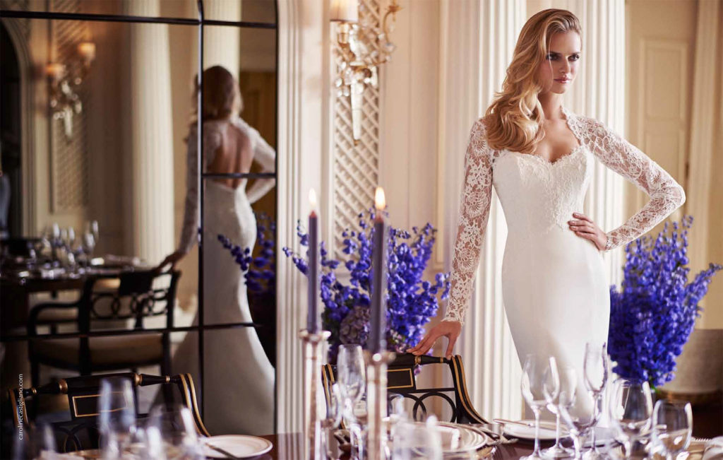 Lady posing in her dressing room in her ivory mermaid style Caroline Castigliano dress with sweetheart neck