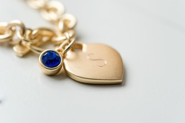 A gold charm bracelet with a sapphire birthstone, from Confetti.co.uk