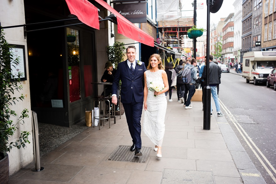 Bride & Groom walking through Soho in London City on their Wedding day | Confetti.co.uk