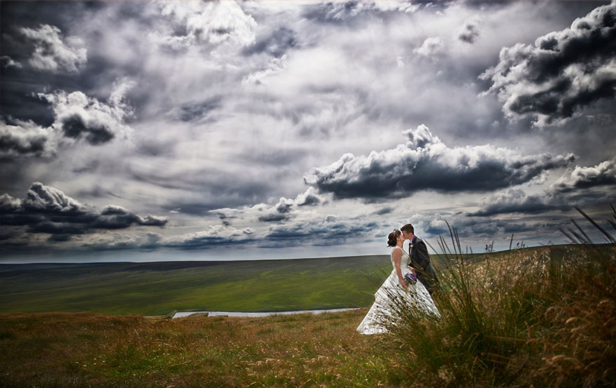 Pennine Manor Kissing Bride and Groom Couple Countryside Photo with Grey Clouds and Moody Sky | Confetti.co.uk