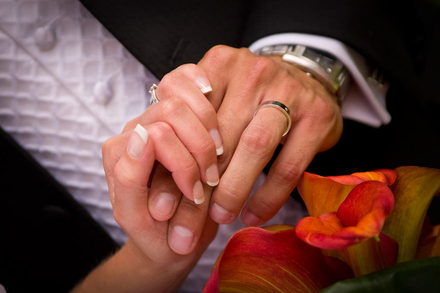 Bride and Groom Holding Hands Wearing Wedding Rings | Confetti.co.uk