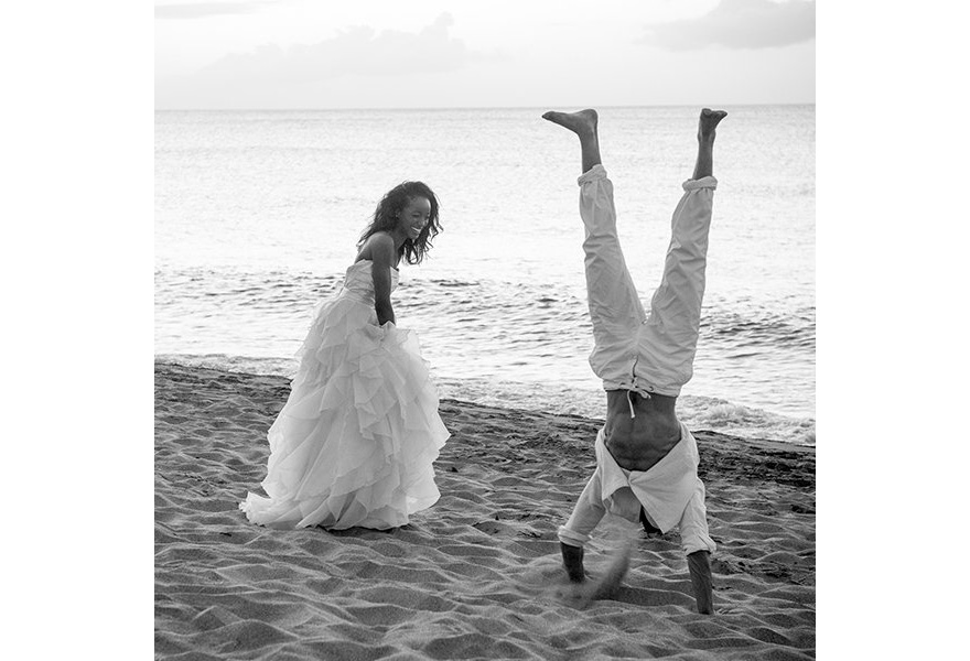 Bride and Groom Laughing on the Beach by Relate Studios - Groom Doing a Hand Stand on the Beach as the Bride Laughs - Beautiful Black and White Wedding Photography | Confetti.co.uk