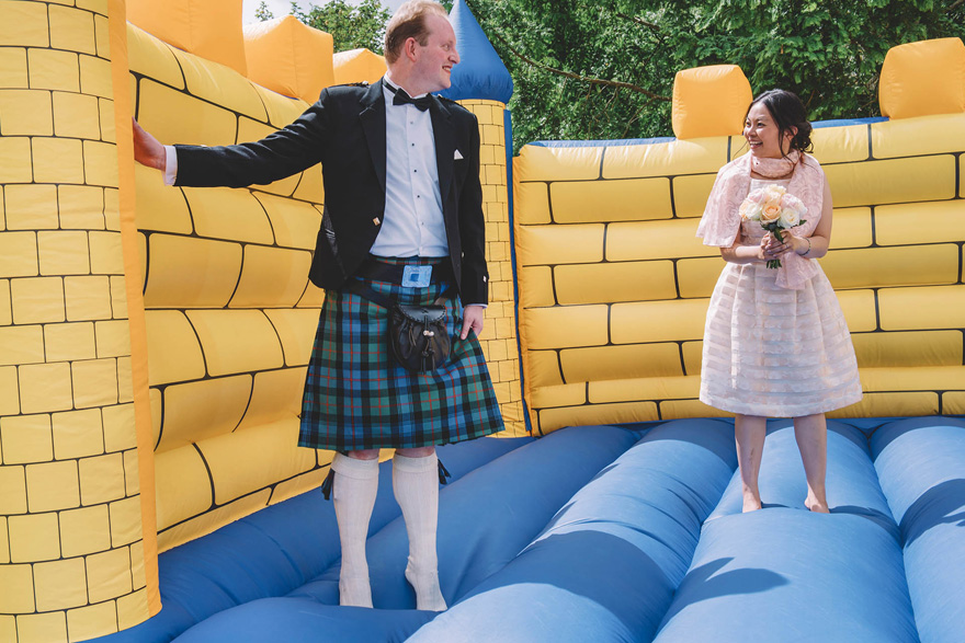 Bride and Groom on a Bouncy Castle Wedding Photo by Emma-Jane Photography | Confetti.co.uk