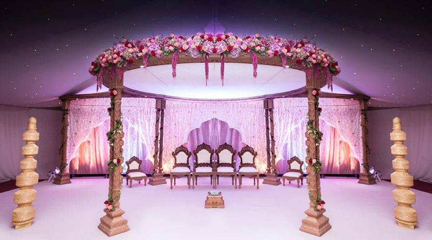 Extravagant Asian Wedding with Ornate Thrones with Flowers and Golden Pillars - Newland Manor Asian Wedding Specialist Wedding Venue - Elaborate Pelaminan Wedding Throne | Confetti.co.uk