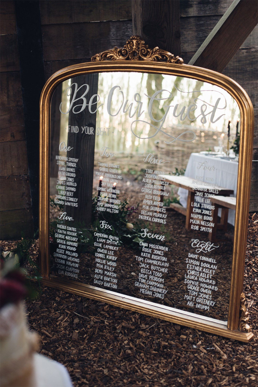 Be Our Guest Beauty and the Beast Style Antique Gold Mirror with Hand Written Calligraphy Table Plan by Sophie Carefull Photography - Mirror Wedding Sign | Confetti.co.uk