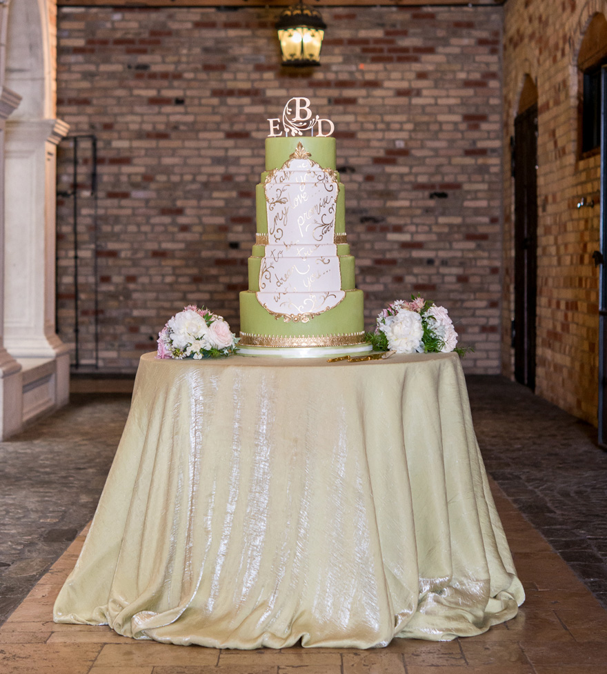 Green and White Tall Tiered Wedding Cake with Gold Script and Monogram Acrylic Cake Topper - Fairytale Wedding Cakes - Wedding Cake Table Ideas | Confetti.co.uk
