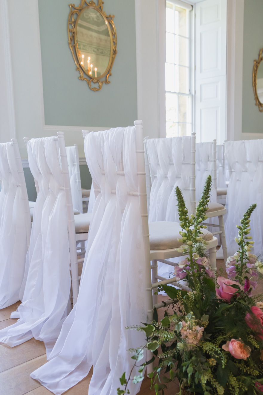 Pretty Wedding Chair Decor - White Wedding Chair Covers - Wedding Ceremony Seating Ideas - Fabric Woven Through Wedding Ceremony Seating | Confetti.co.uk